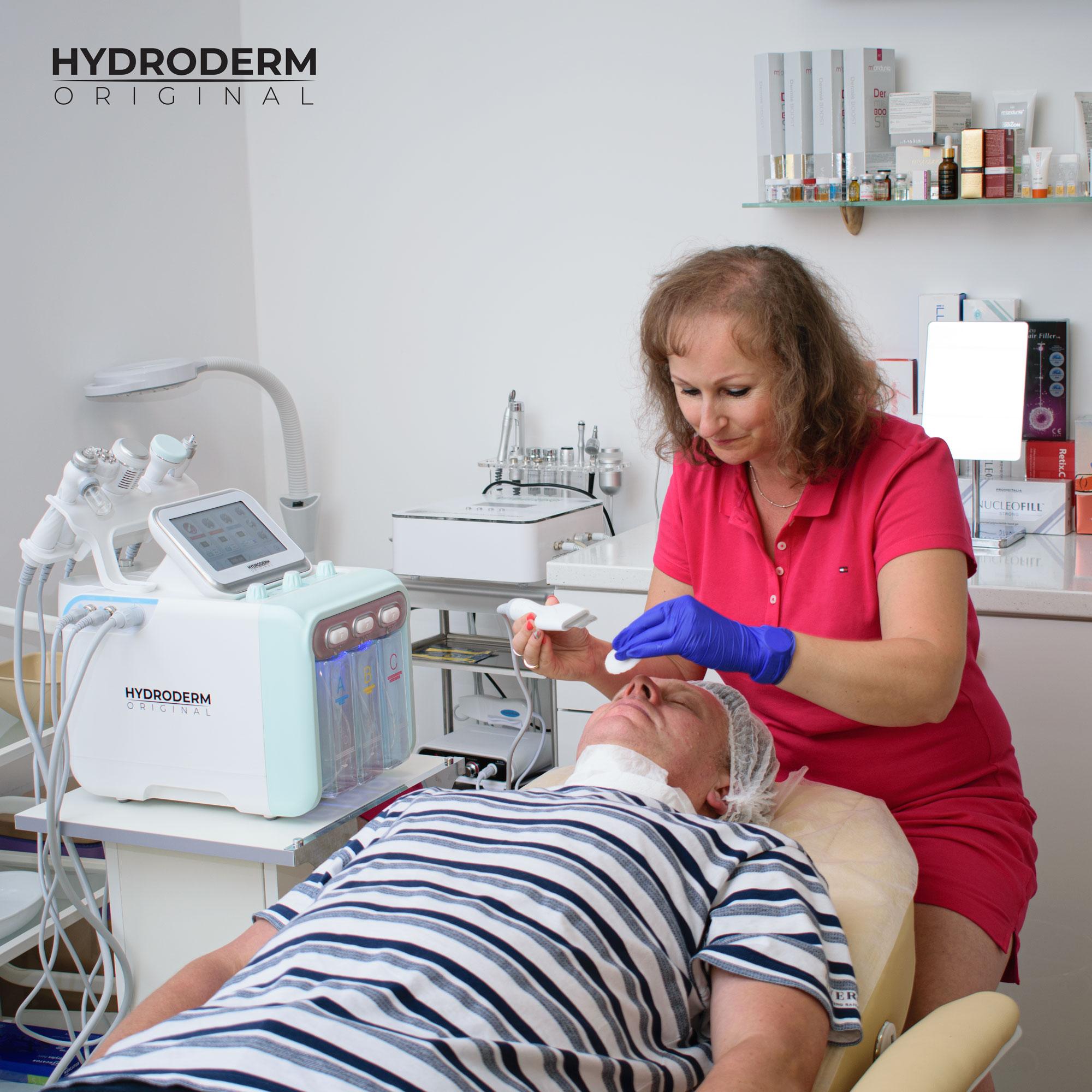 Uczestniczka szkolenia powoli oczyszcza powierzchniowe warstwy skóry na twarzy pacjenta